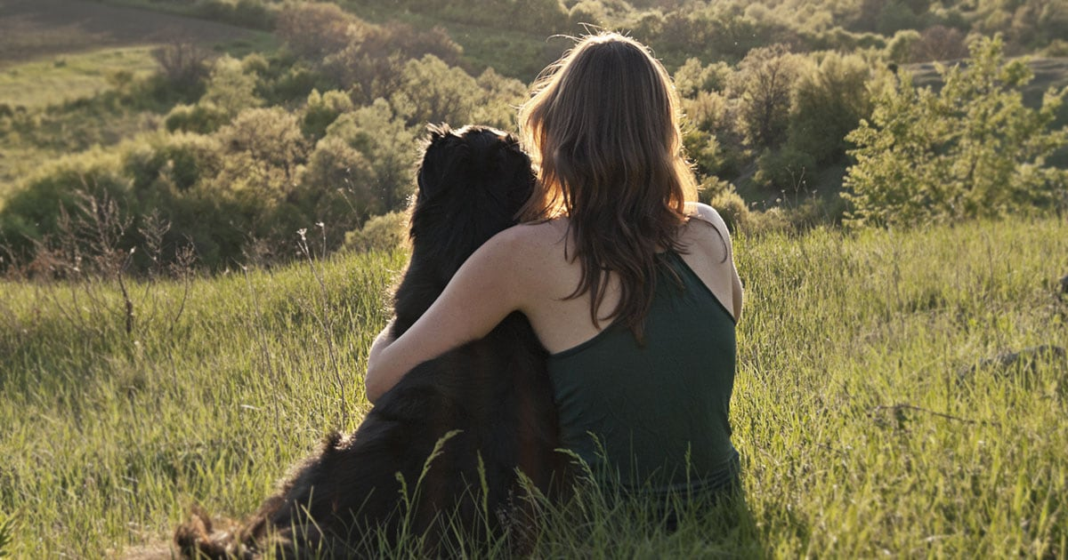 Woman and Black Dog Sitting on a Hill Overlooking a Forest | Diamond Pet Foods