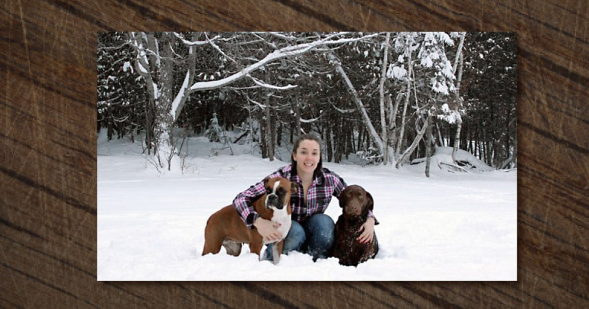 Woman with Two Dogs Sitting on the Snow | Diamond Pet Foods