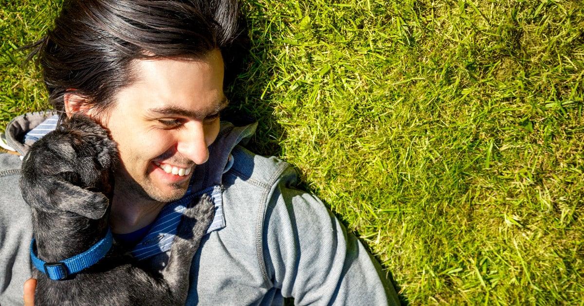 Close-Up of Man Lying on Grass with Dog | Diamond Pet Foods